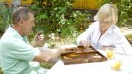Elderly couple playing backgammon in the garden. video