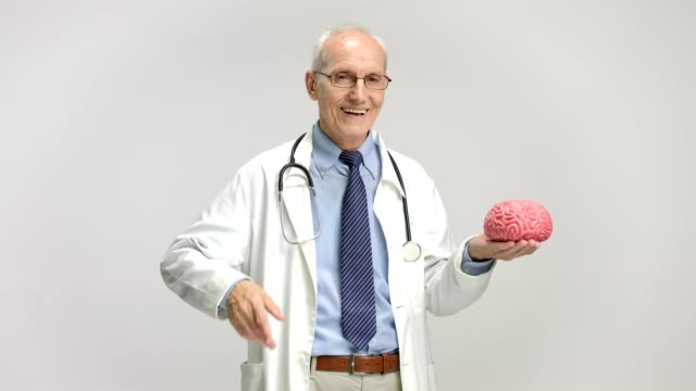 Elderly doctor holding a brain model and pointing up video