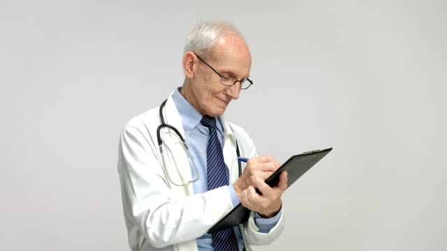 Elderly doctor writing in a clipboard and smiling video