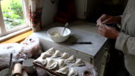elderly hand make dumplings with filling in rural kitchen video