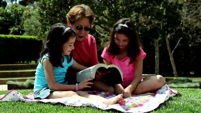 Elderly Lady Reads to Young Girls Outdoors video