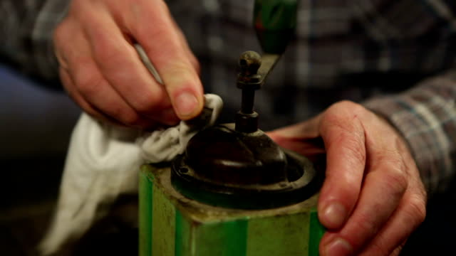 Elderly man cleaning a coffee mill video