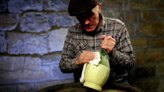 Elderly man cleaning a wine bottle video
