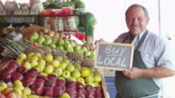 Elderly man holding sign saying buy local from fruits market video