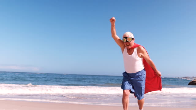 elderly man running with the arms in the air dressed like superheros video
