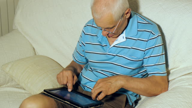 Elderly man uses tablet video