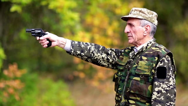 Elderly person in military uniform shoots a revolver video