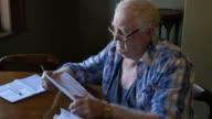 Elderly retired man sitting at desk looking at overdue bills video