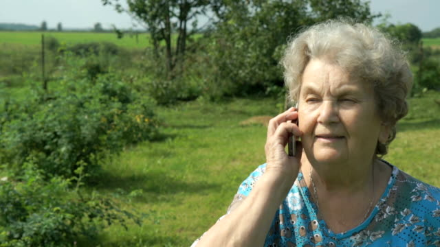 Elderly woman 80s communicates cell phone outdoors video