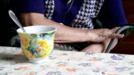 Elderly woman at the table with a cup of drink video