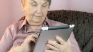 Elderly woman holding the silver tablet computer video