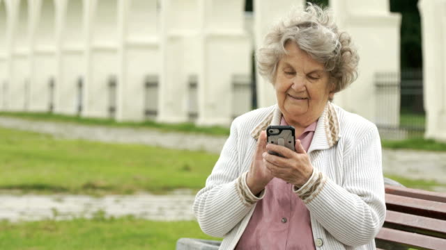 Elderly woman holds silver smart phone outdoors video
