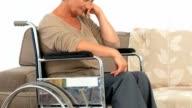Elderly woman in a wheelchair thinking video