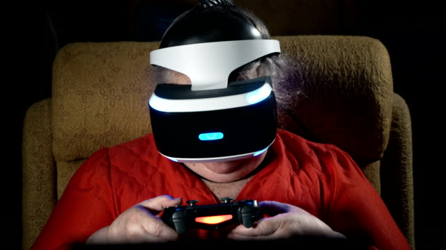 Elderly woman in front of TV screen uses VR headset and wireless gaming controller video