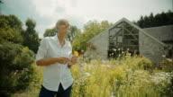 Elderly woman in garden smelling on flower video