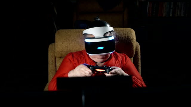 Elderly woman in VR headset playing virtual reality game in front of TV screen video