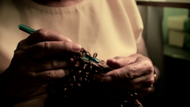Elderly woman knitting with needles video