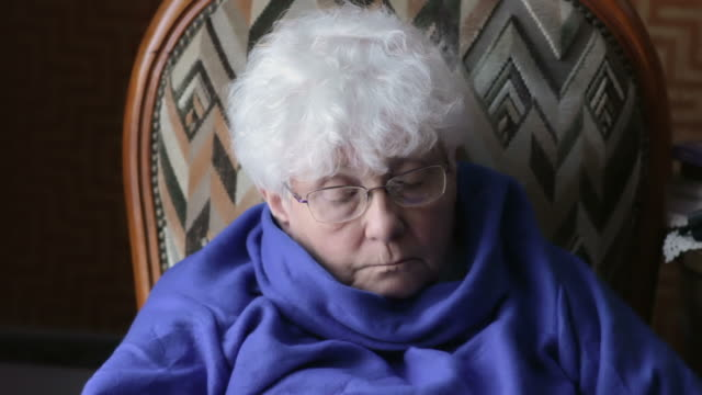 Elderly woman looking at electronic device video