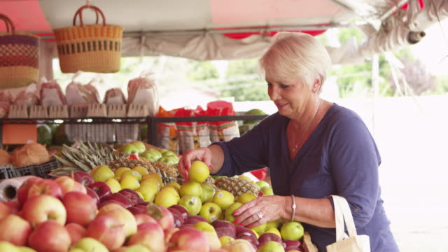 Elderly woman looking at fresh fruits and vegetables video
