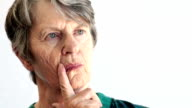 Elderly woman looks stressed and deep in thought as she looks slightly away from the camera, rubbing her face and raising her eyebrows. video