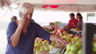 Elderly woman on cellphone buying fresh fruits at market video