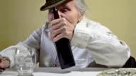 Elderly woman opens bottle of dark beer. video