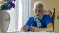 Elderly woman praying with rosary beads, crucified Christ, cross, old video