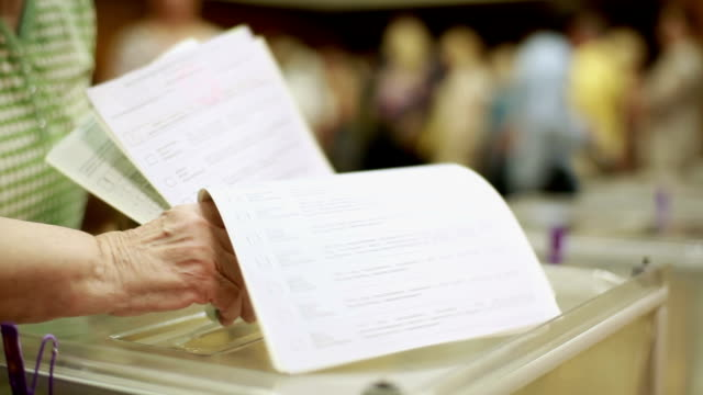 elderly woman puts electoral billeting in the ballot box. Only hands. video
