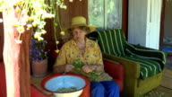 elderly woman reap chamomile in bowl in armchair outdoors video