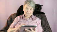 Elderly woman sits at armchair next to black cat video