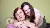 elderly woman sitting in chair hugging her girl video