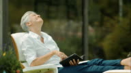 Elderly woman sitting in garden and reading video
