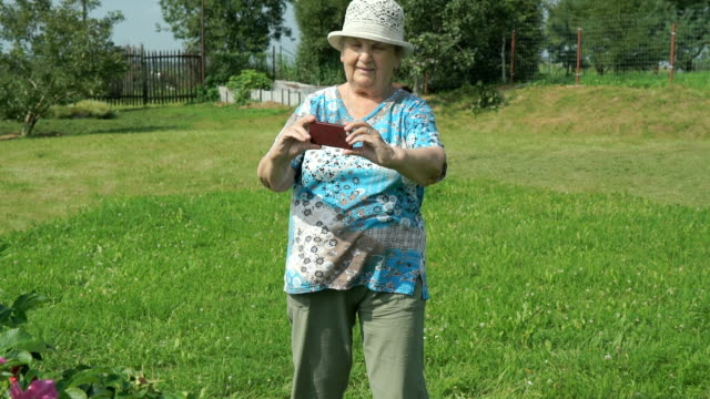 Elderly woman taking photos the nature of park video