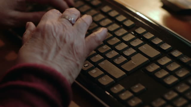 Elderly woman typing at computer video