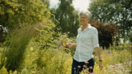 Elderly woman walking through garden and smelling on flower video