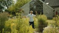 Elderly woman walking through garden and spinning video