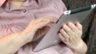 Elderly woman with digital tablet computer indoors video
