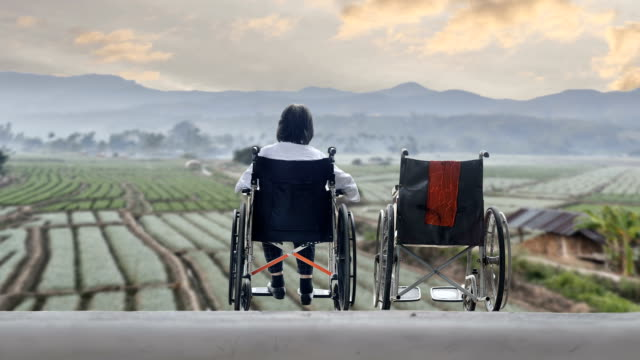 Elderly woman with empty wheelchair standing together video