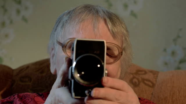 Elderly woman with retro camera at home video