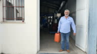 Eldery man standing with canister at the entrance to the factory video