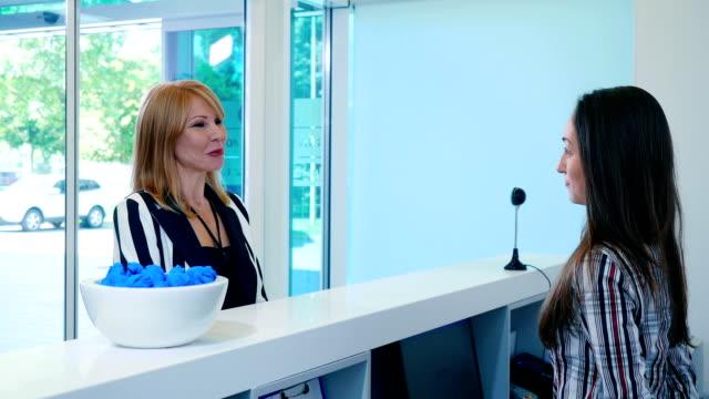 Eldery woman talking with receptionist in clinic video