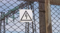 Electric high-voltage substation beyond the fence. Hazard warning sign. Danger to life. Energy industry. Electric wires on the support. Risk of electric shock video