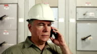 electrical engineer on the phone smiles at camera video