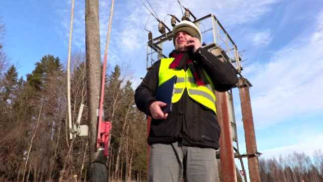 Electrician engineer using smart phone at transformer video