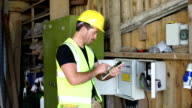 Electrician / Inspector with Digital Tablet at Fuse Box video