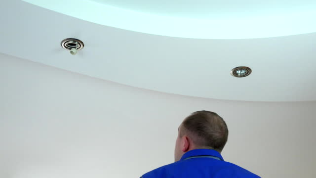 electrician man install or replace halogen light lamp into ceiling video