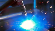 Electro welding working at the factory for the production of metal parts. Welding process is shot close-up video