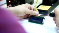 Electronic technician soldering on a electronic board video