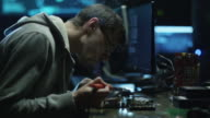 Electronics engineer is soldering an electric board with processors in a dark office with display screens. video