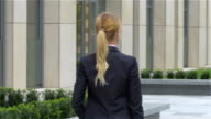 elegant blonde business woman with tablet computer goes around office building. slow motion video